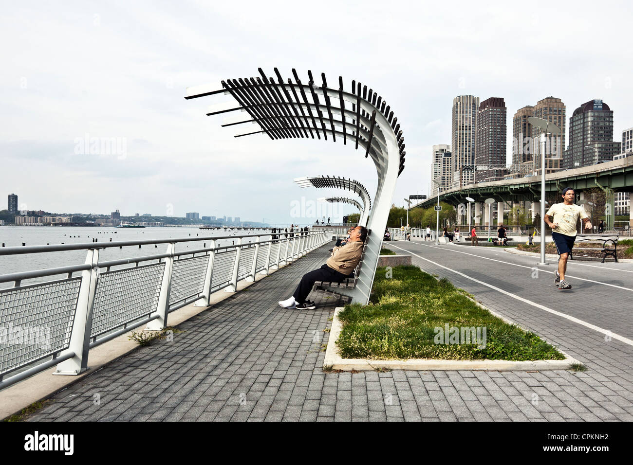 man snoozes on bench with shade canopy on Riverside Park esplanade as runner passes in front of West Side Highway - Stock Image