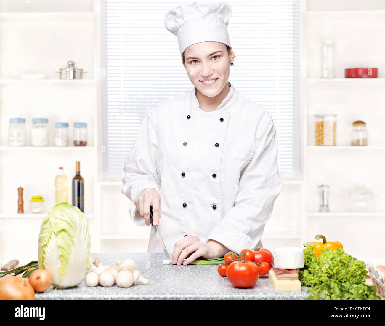 Young female chef cutting onions in kitchen - Stock Image