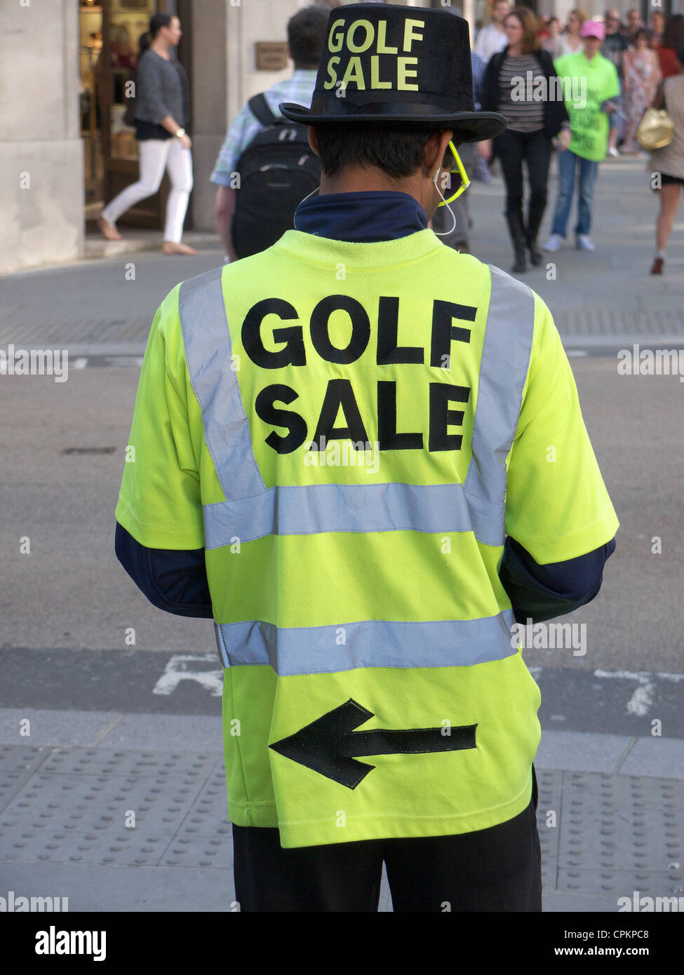 A person standing wearing adverts for a golf sale - Stock Image