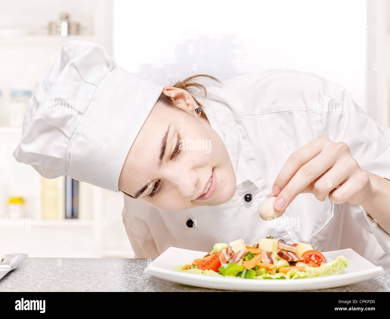 pretty young chef decorating delicious salad - Stock Image