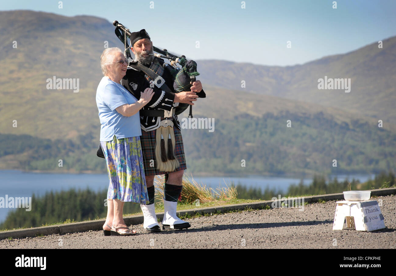 A TOURIST POSES FOR PHOTOGRAPHS WITH A SCOTTISH PIPER AND HIS COLLECTION CONTAINER AT A VIEWPOINT IN SCOTLAND RE - Stock Image