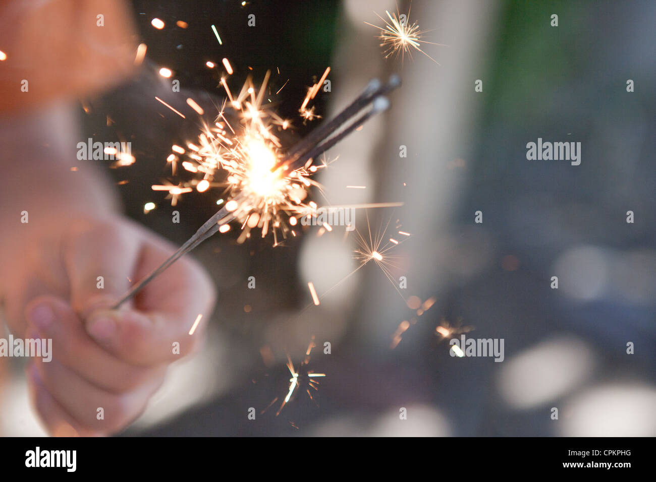 Closeup of a child holding multiple sparklers burning. - Stock Image