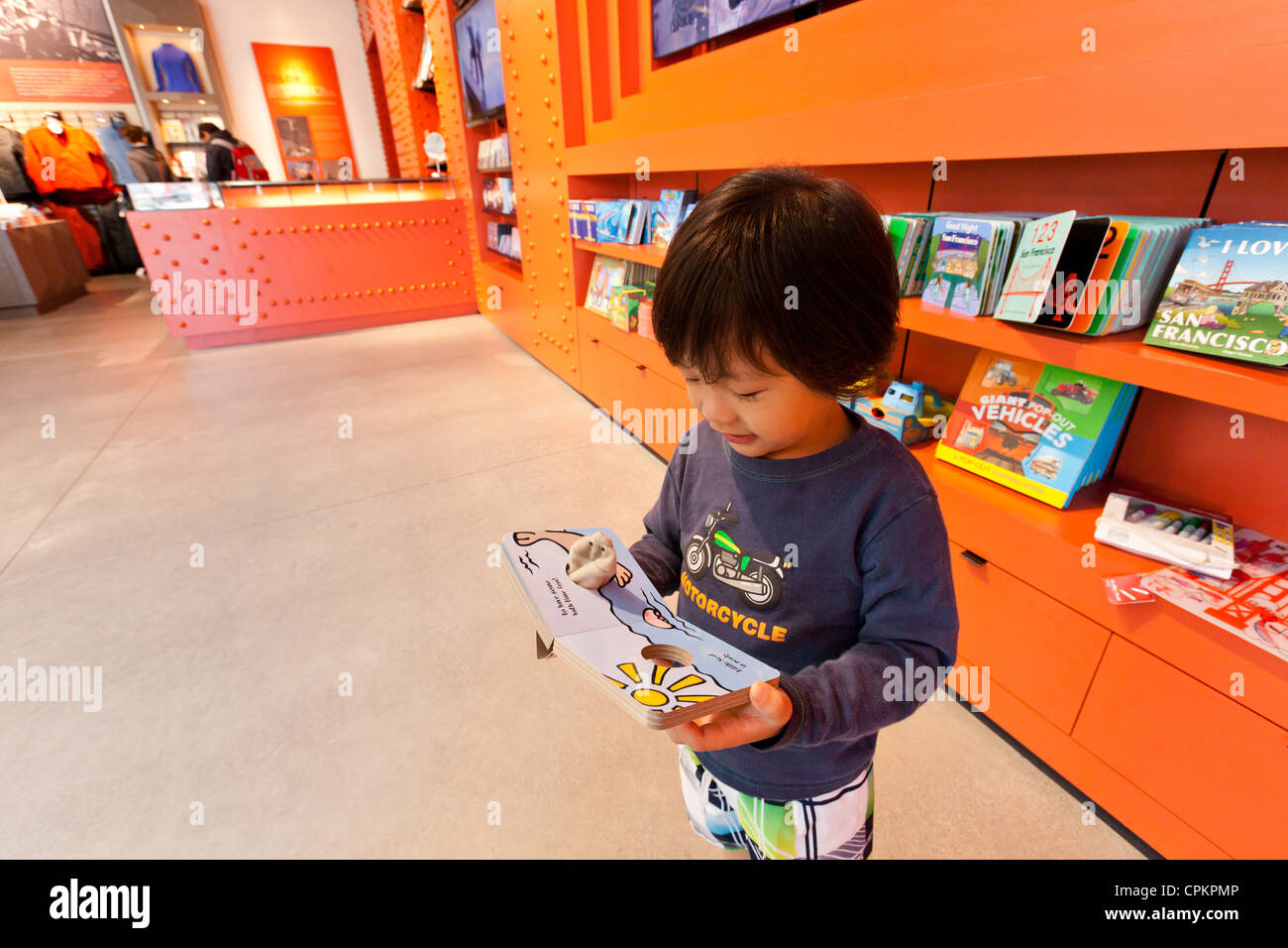 A small Asian boy reading a children's book in the bookstore - Stock Image