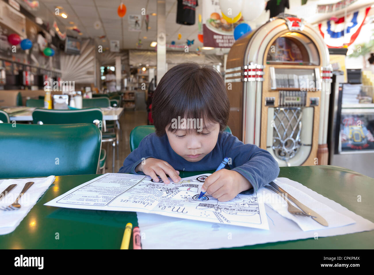 A young Asian boy coloring a children's diner menu - Stock Image
