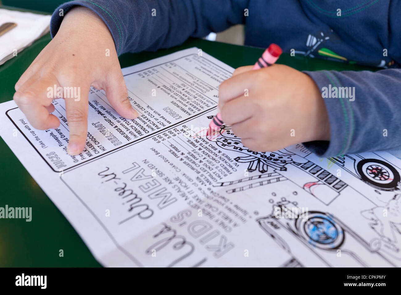 Closeup of a young boy coloring a children's diner menu - Stock Image