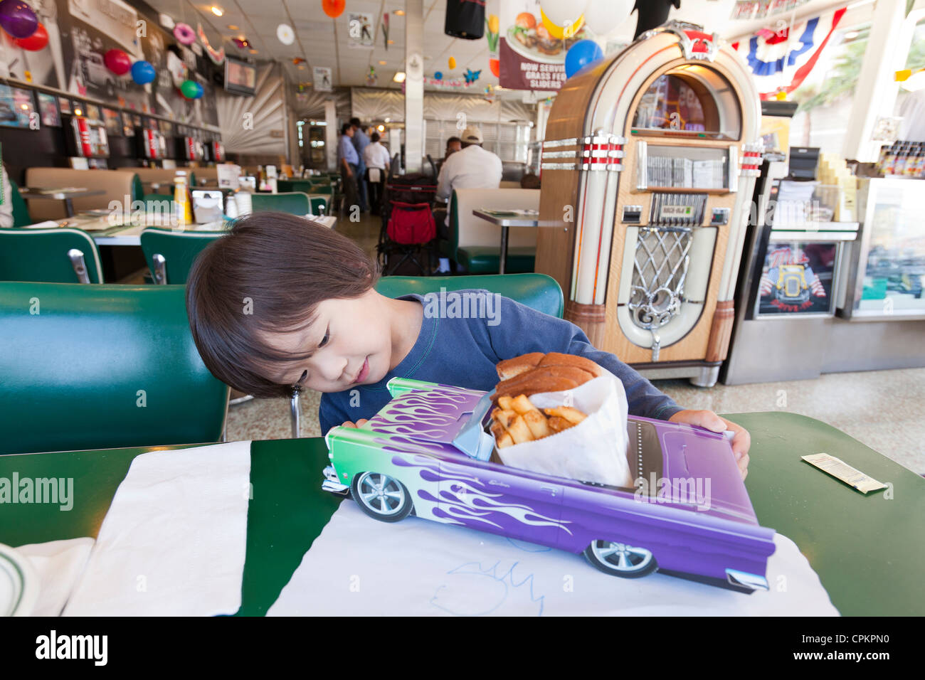 A small Asian boy looking at a car model serving plate in a diner - Stock Image