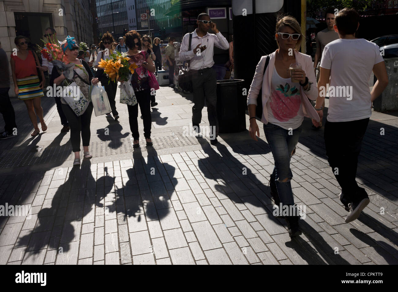 Visitors to the RHS Chelsea Flower Show make their way home through Sloane Square after the last day's plant sell Stock Photo