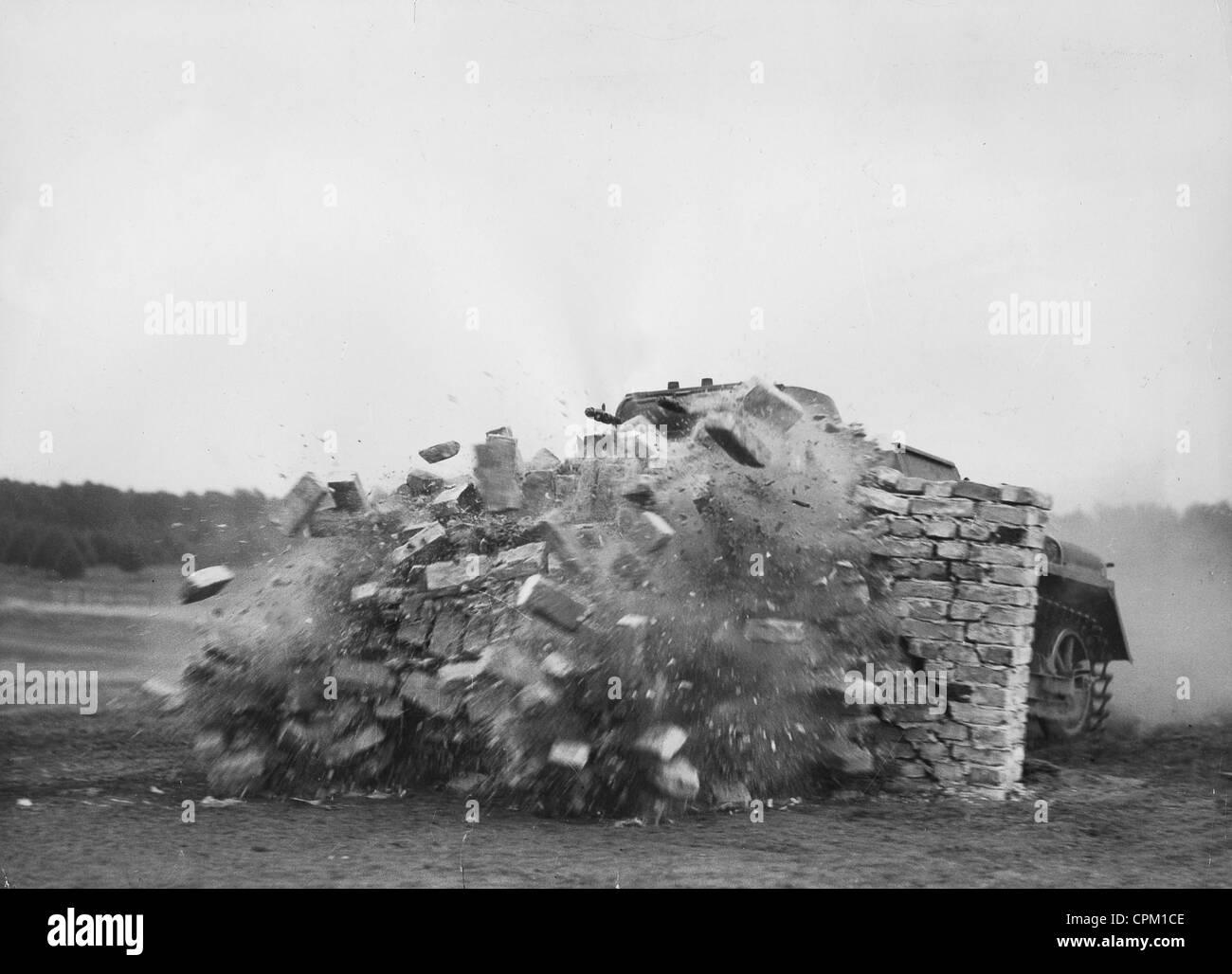 Panzer I breaks through a brick wall, 1936 - Stock Image