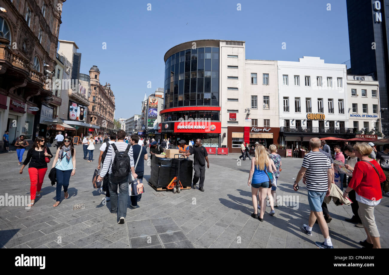 People walking by Leicester Square, London, England, UK - Stock Image