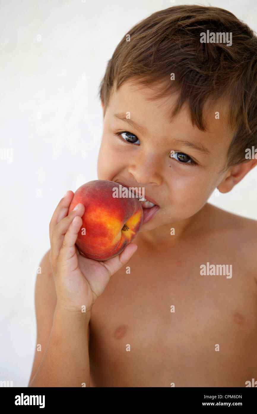 CHILD EATING FRUIT - Stock Image