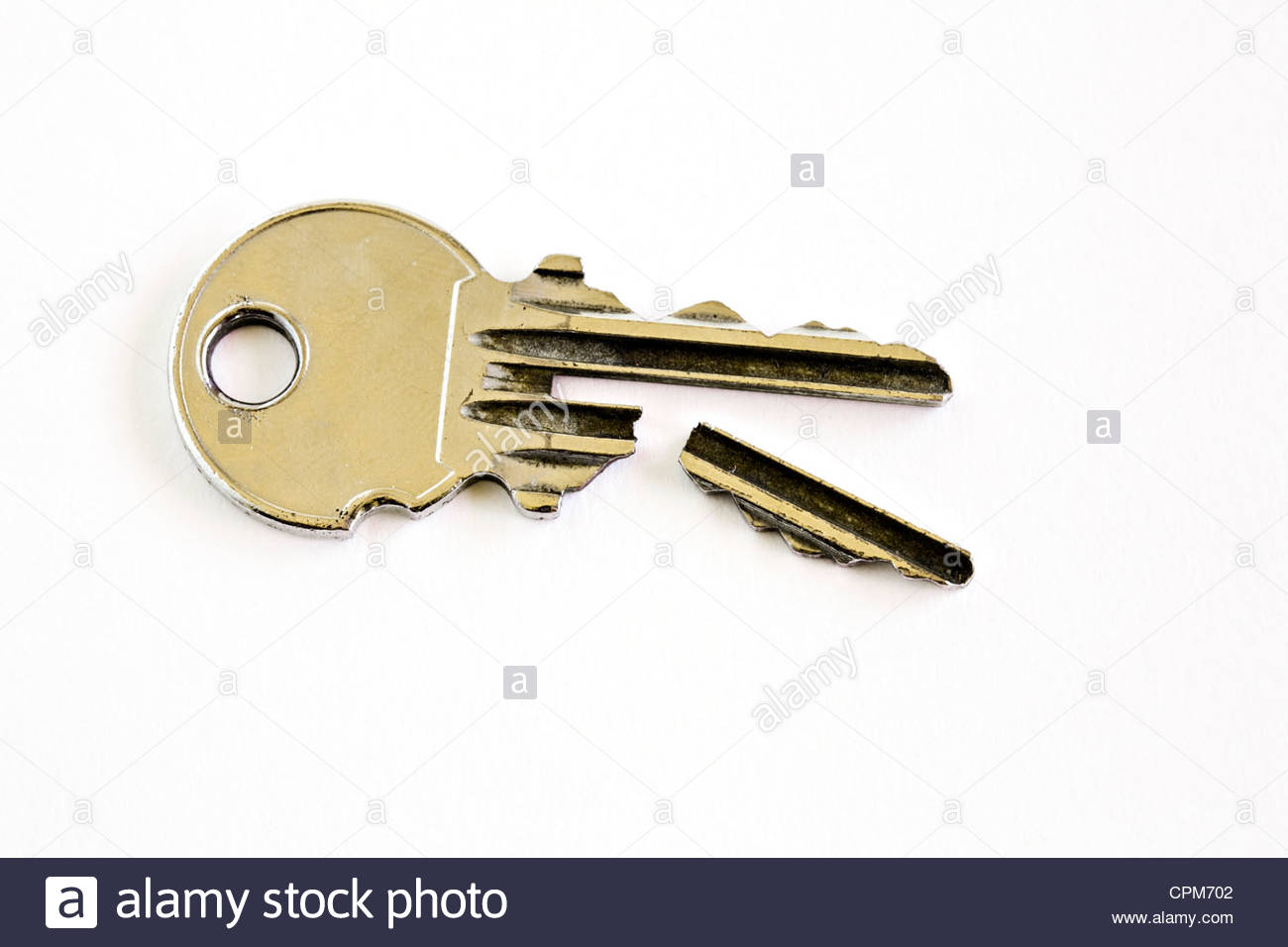 Close-up of broken key on white background - Stock Image
