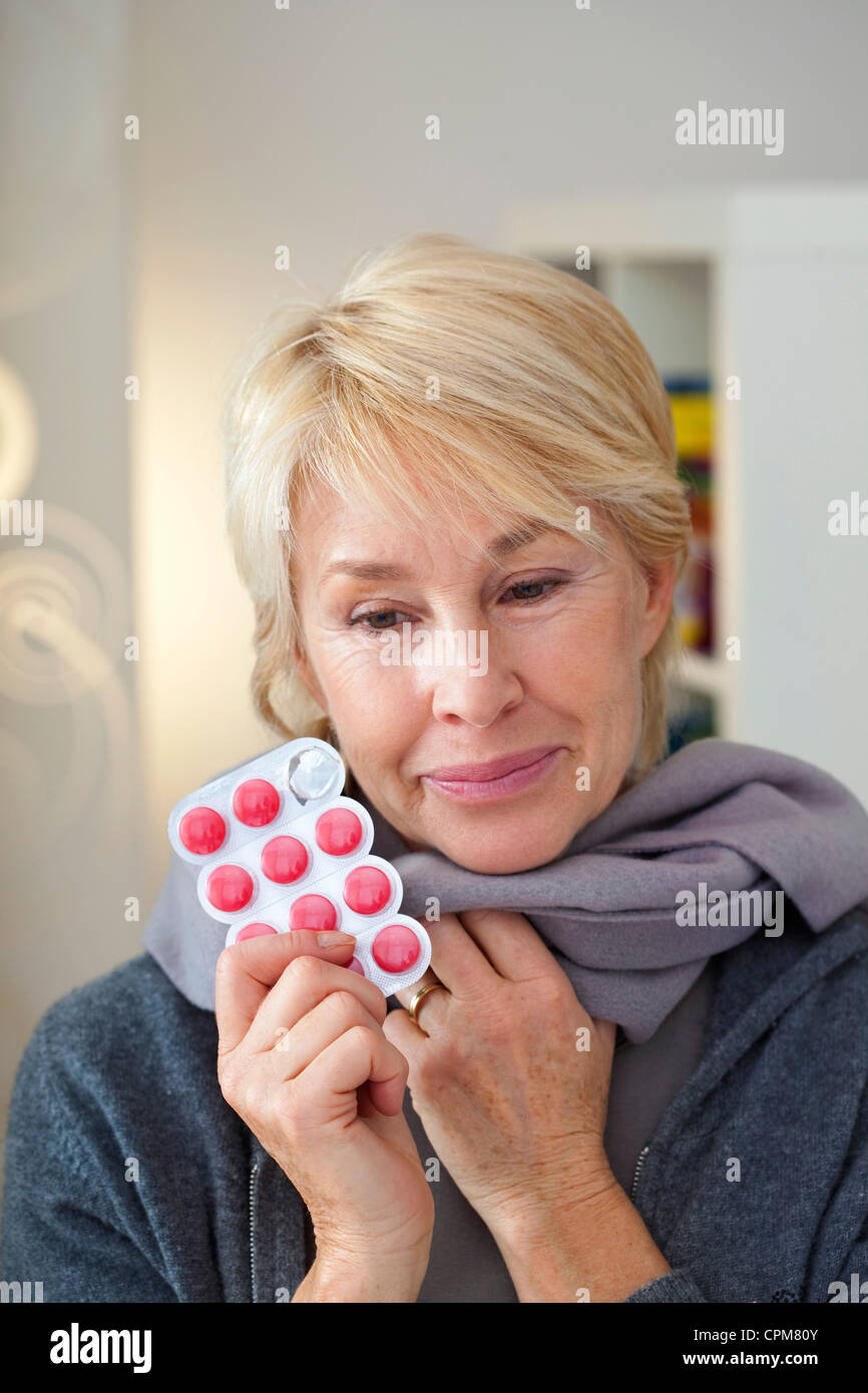ELDERLY PERSON TAKING MEDICATION - Stock Image
