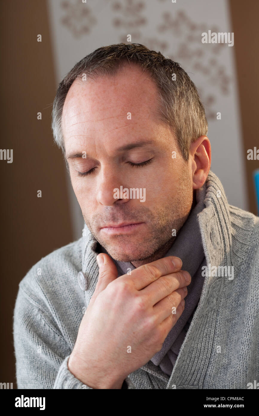 MAN WITH SORE THROAT - Stock Image
