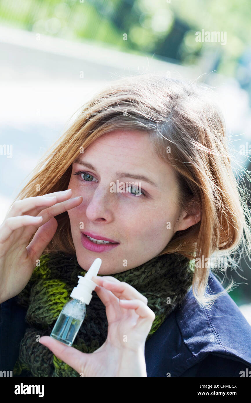 WOMAN USING NOSE SPRAY - Stock Image