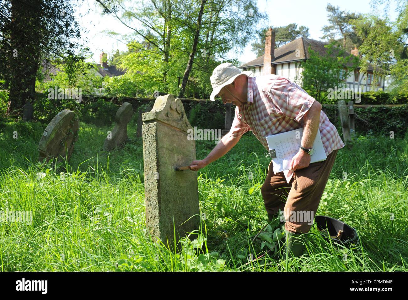 Genealogist David Petley-Jones cleaning a gravestone at Worthen church yard Uk - Stock Image
