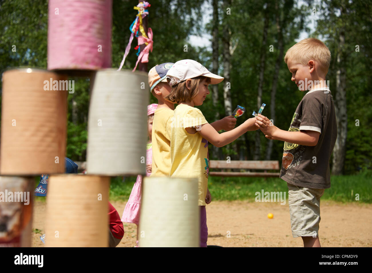 Children throw with small ball on pyramid of cans - Stock Image