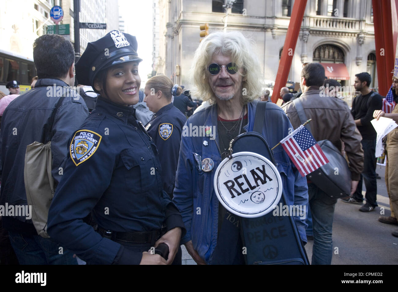 Occupy Wall Street demonstrator stands for a photo with an NYPD officer at Zuccotti Park, aka Liberty Square in - Stock Image