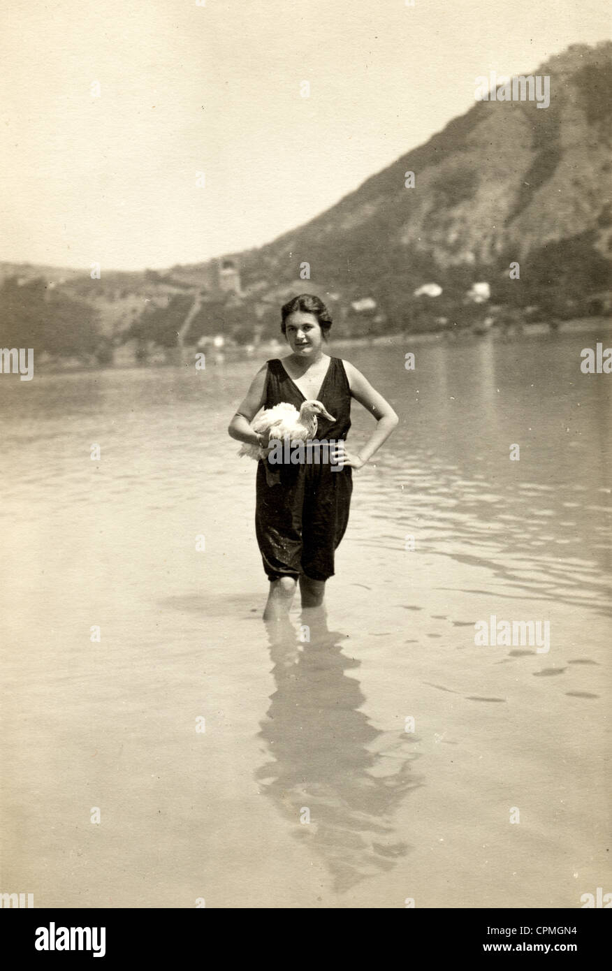 Woman Bather in a Lake Holding Pet Duck - Stock Image