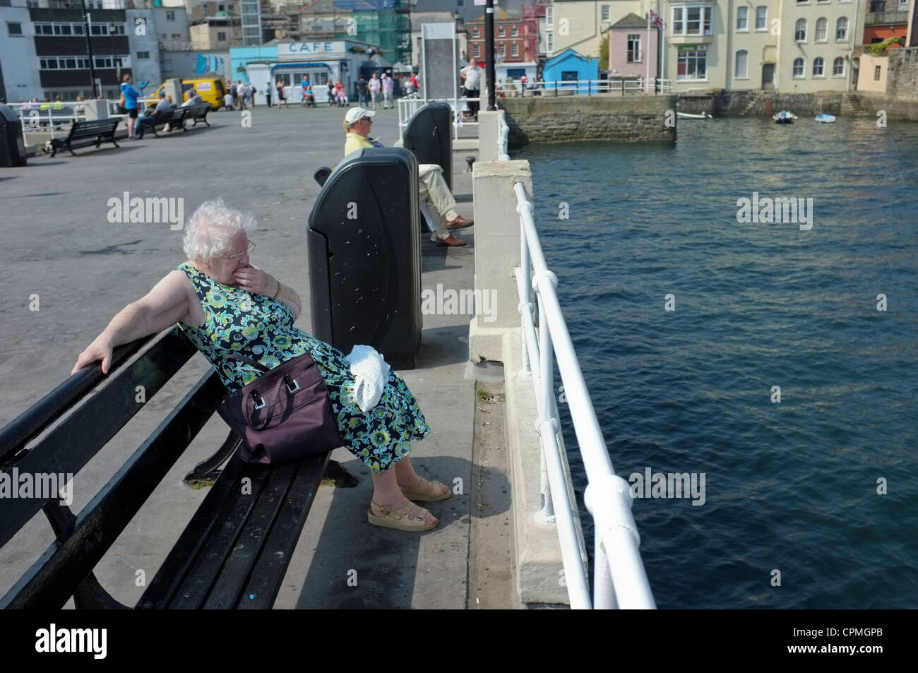 An old lady on a pier in Falmouth, UK - Stock Image