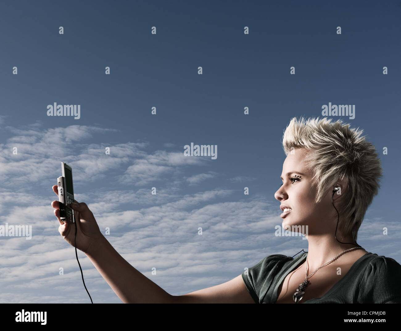Woman looking at mobile phone, wearing headphones, backgrounded by dusk sky - Stock Image