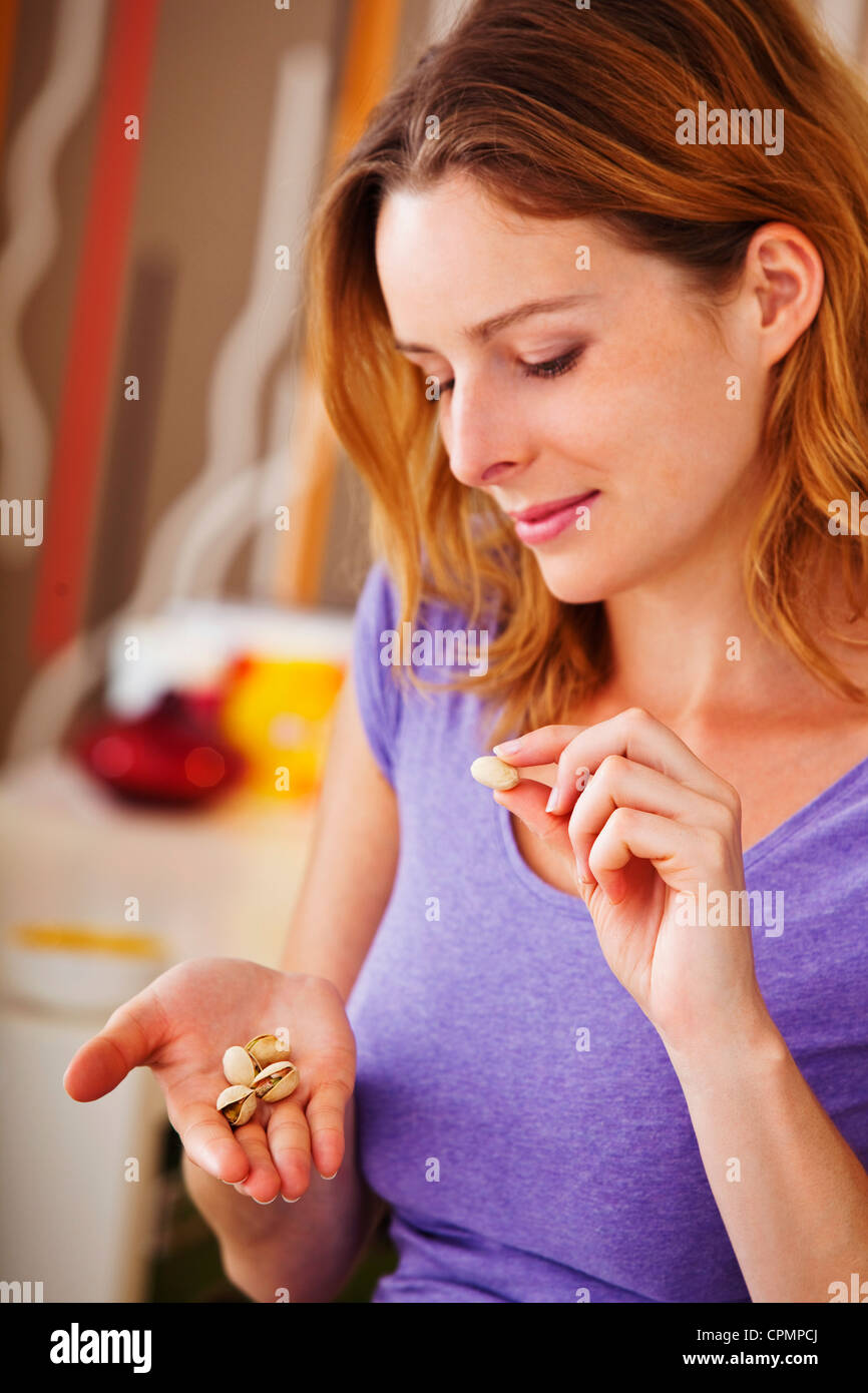 WOMAN EATING DRIED FRUIT - Stock Image