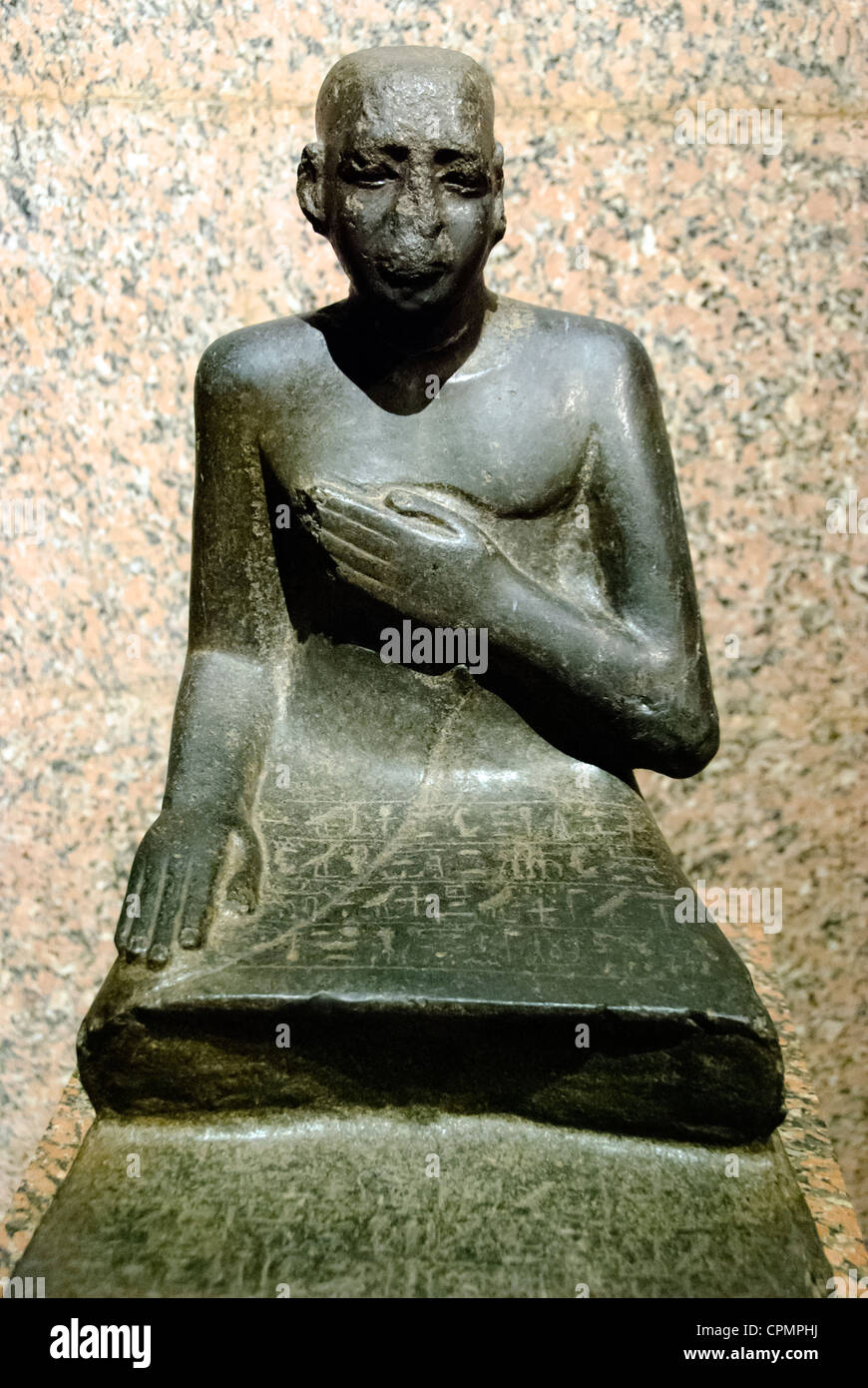 Statue of Senpu, warden of the hall of Amenemhat . His left hand placed across the chest still reflects in the village - Stock Image