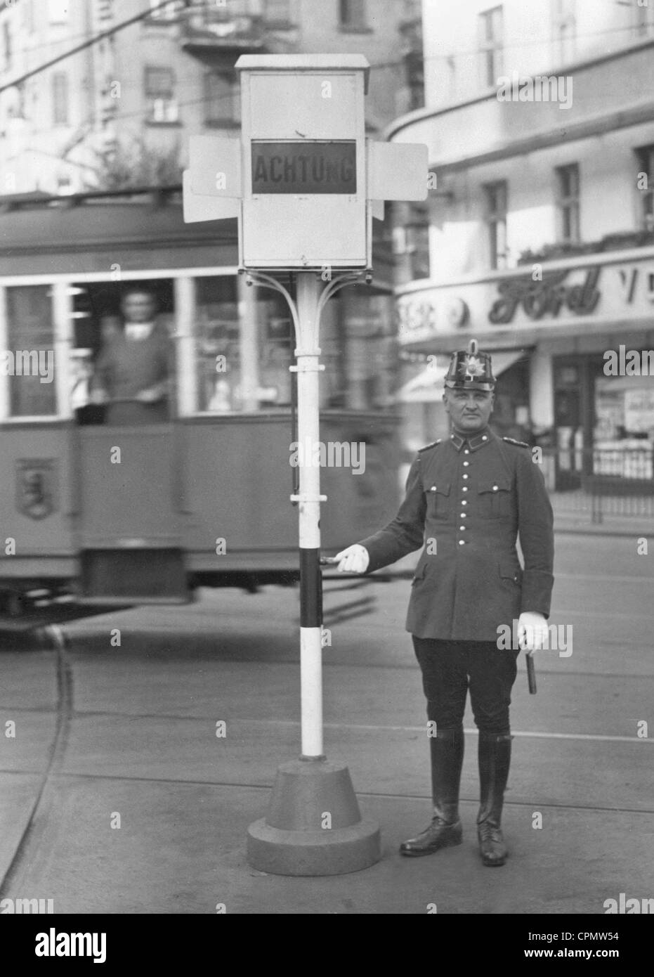 Policeman operates new streetlight on Hermannsplatz - Stock Image