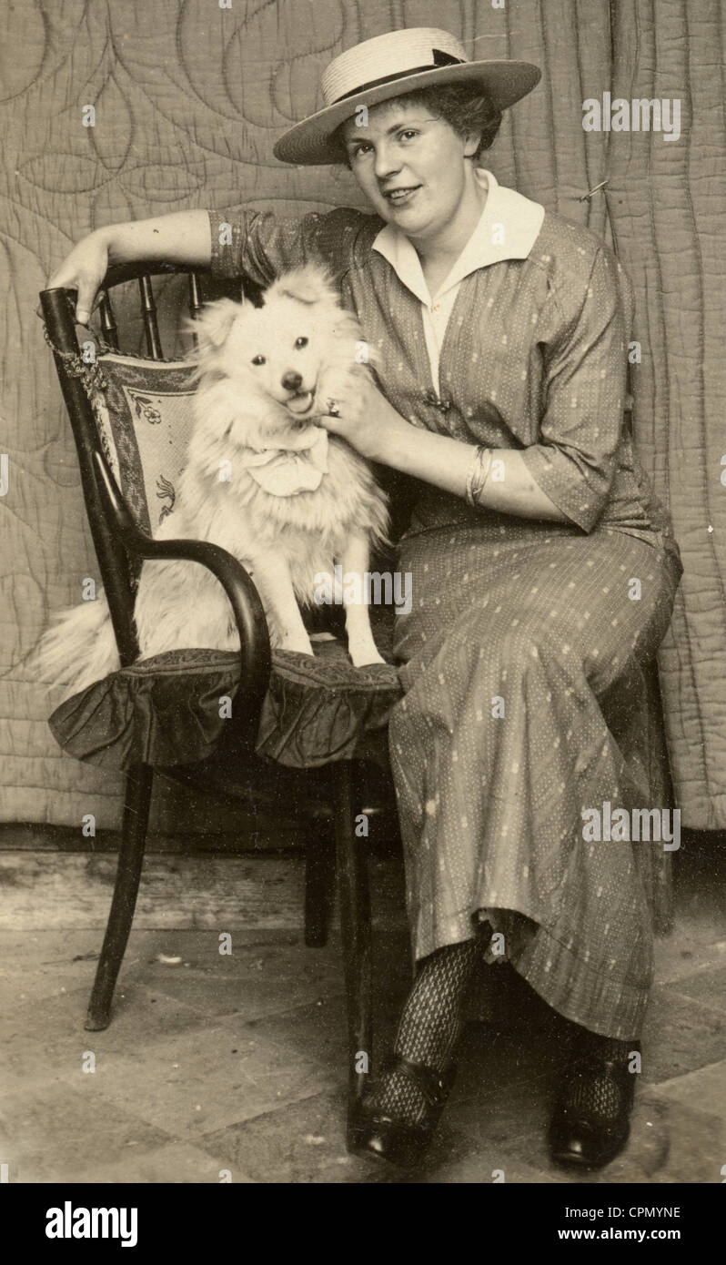 Fashionable Woman Seated with Small Dog on Chair - Stock Image