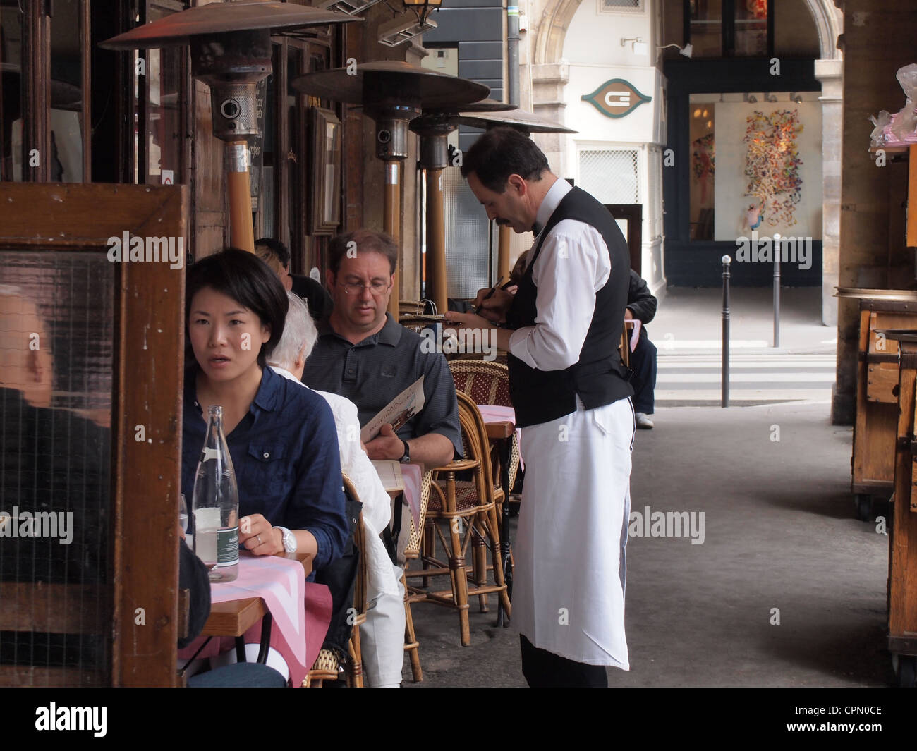 French waiter takes order from customer at a restaurant in Paris, France, May 9, 2012, © Katharine Andriotis - Stock Image