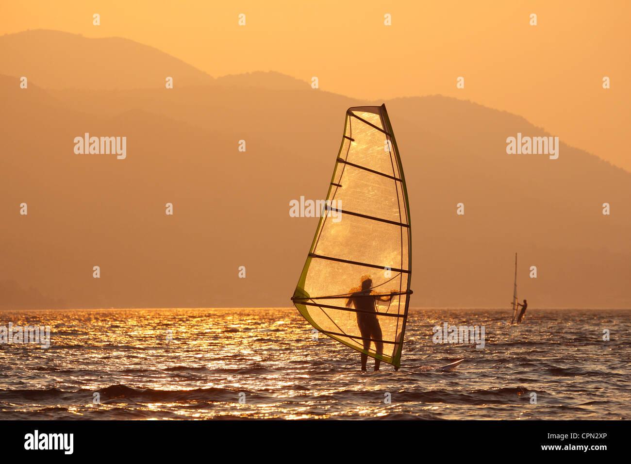 Windsurfing at sunset - Stock Image