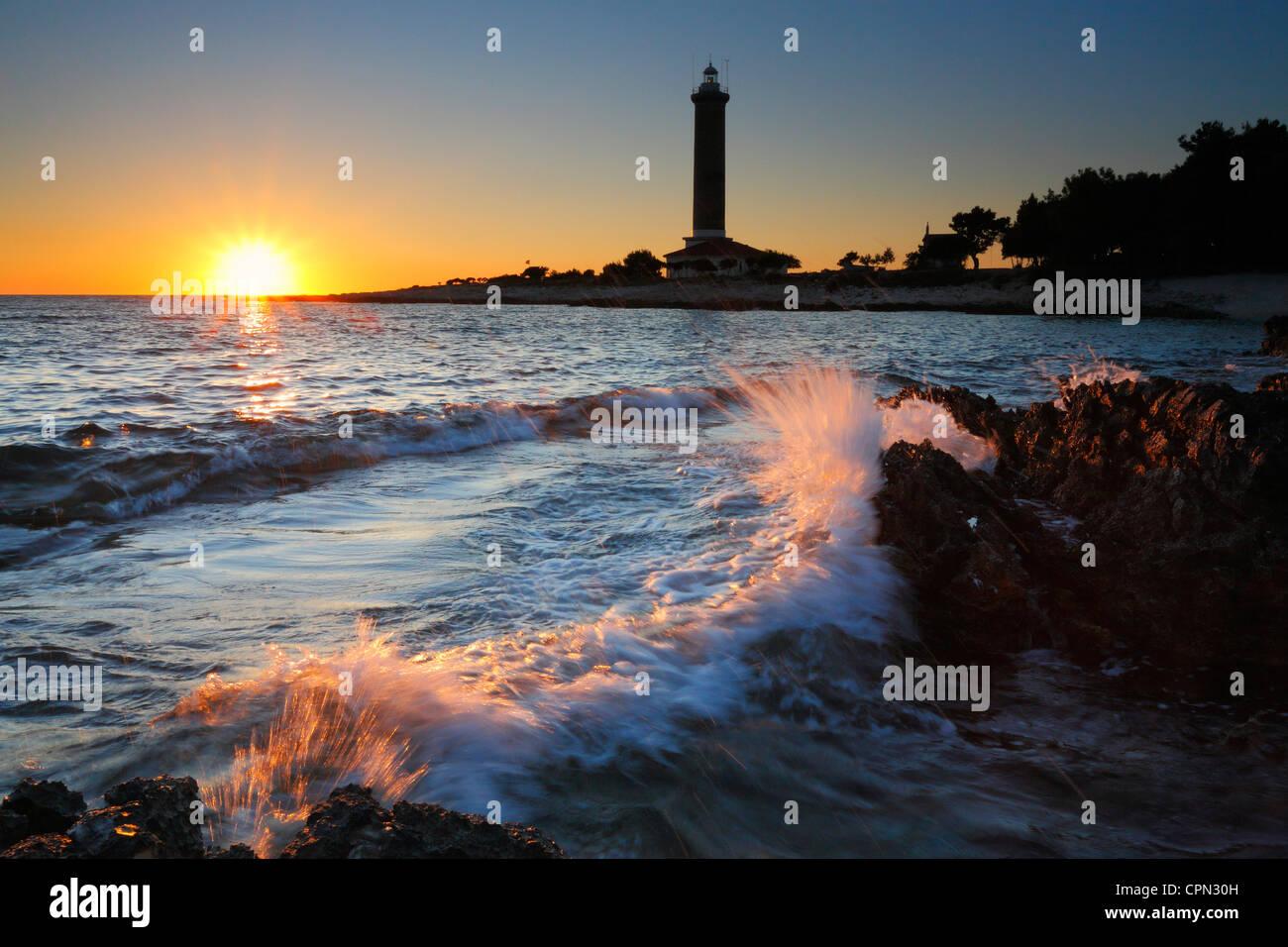 """Sunset at Veli rat on """"Dugi otok"""", Croatia. Waves splashing rocks on the beach. Stock Photo"""