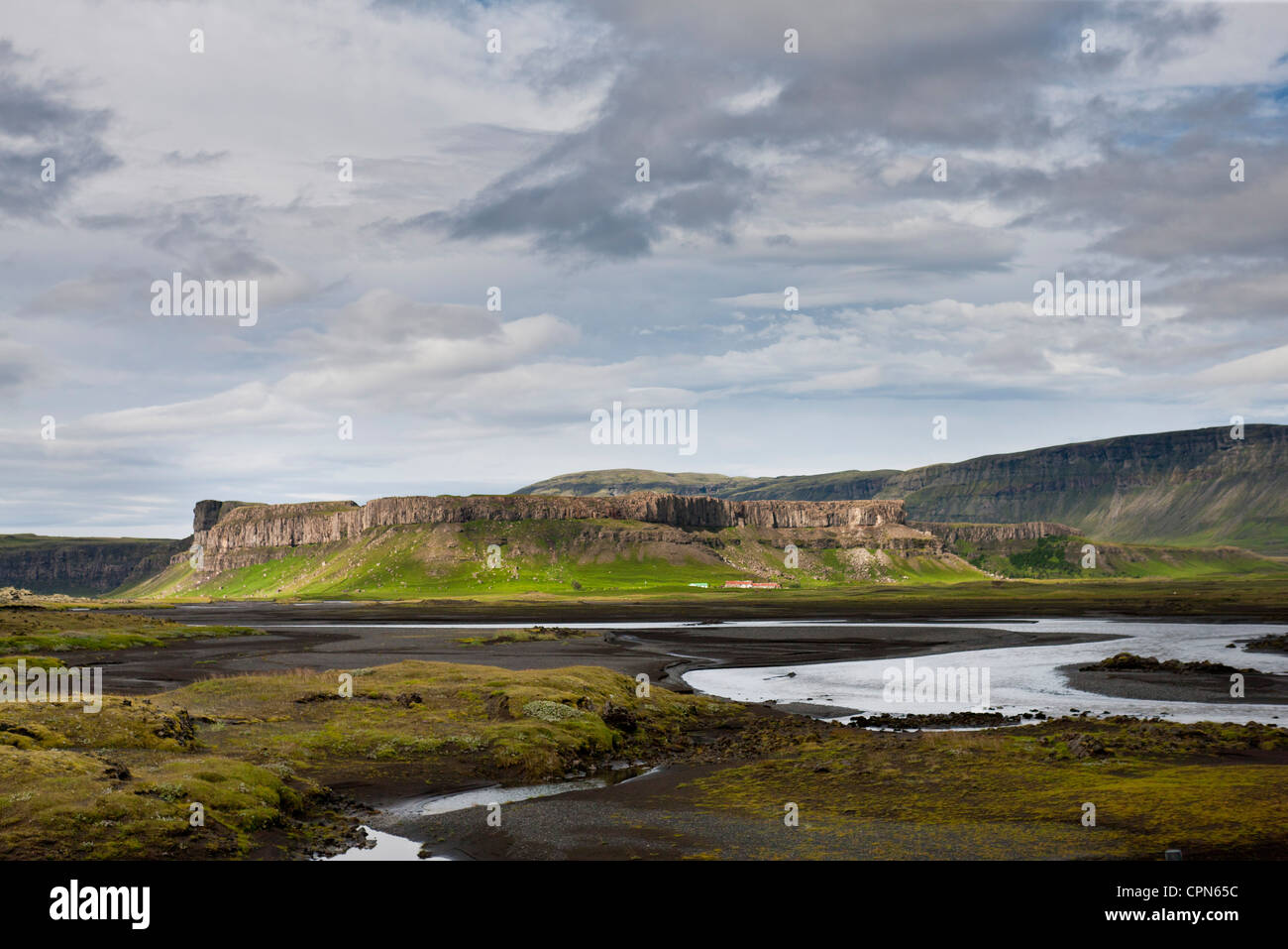 Iceland, stream running through lava field, basalt cliffs in the distance - Stock Image