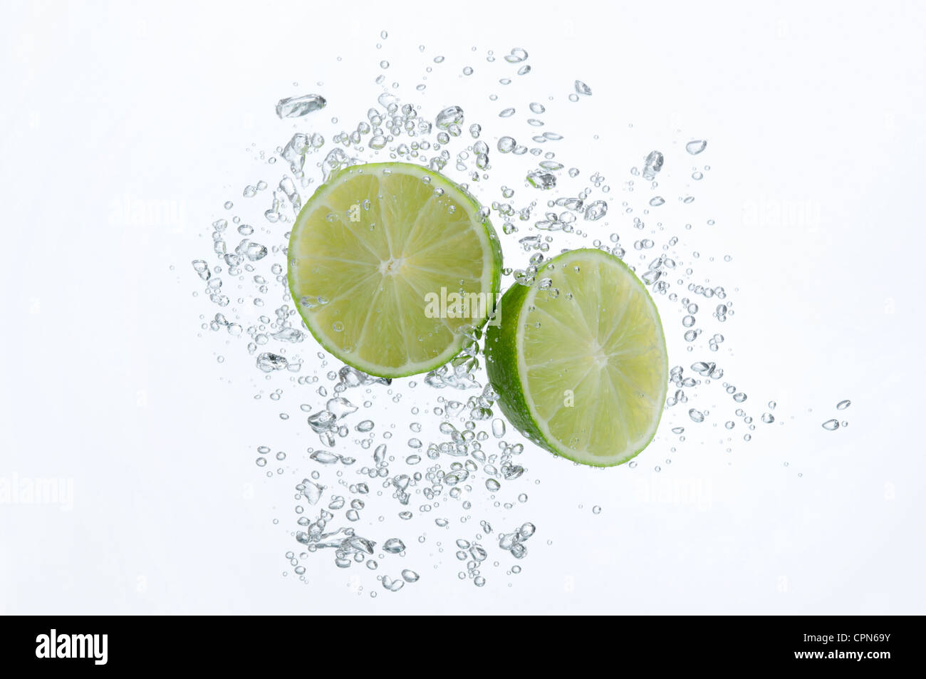 Lime halves submerged in sparkling water - Stock Image