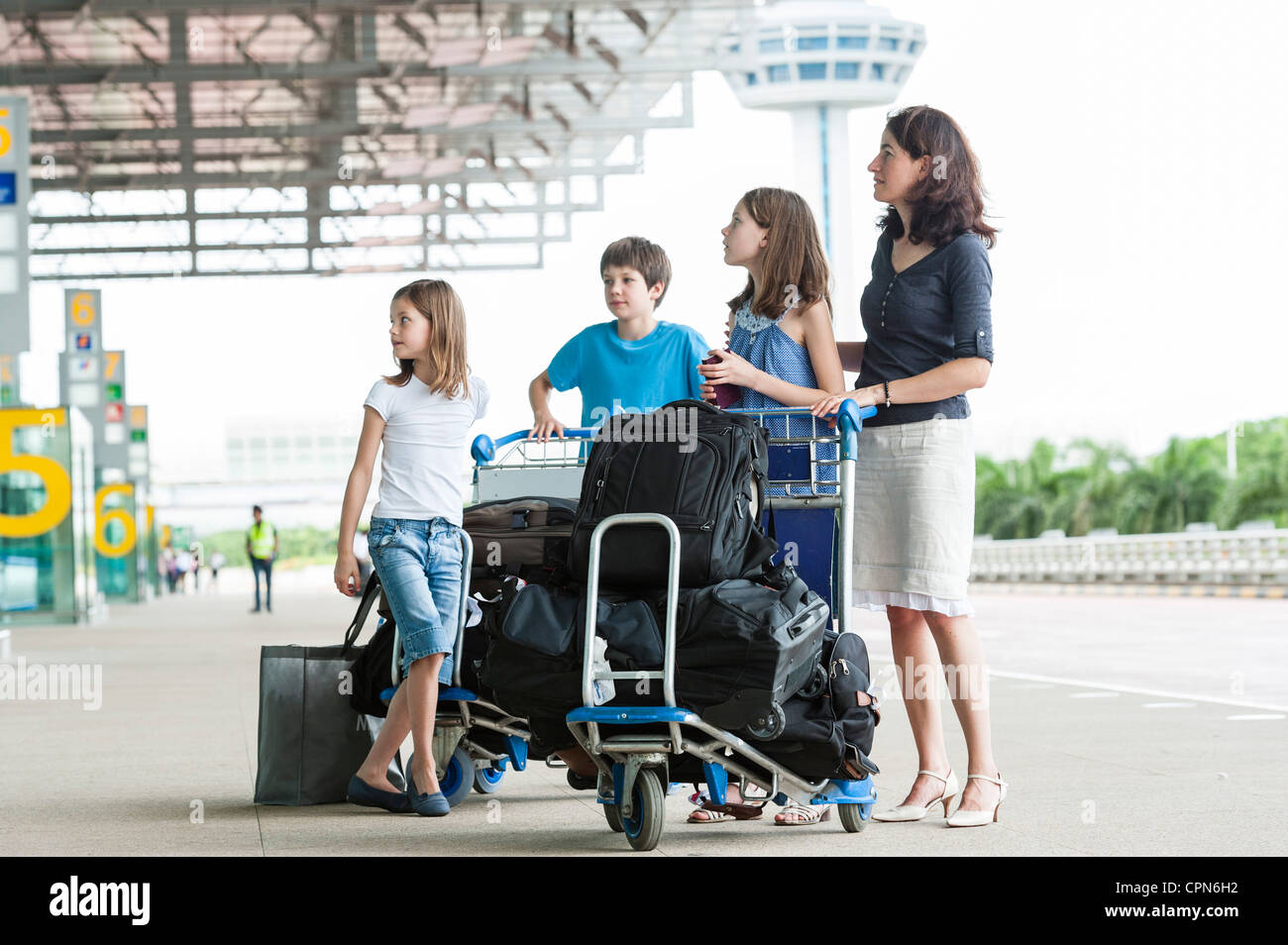 Family standing outside of airport with luggage - Stock Image
