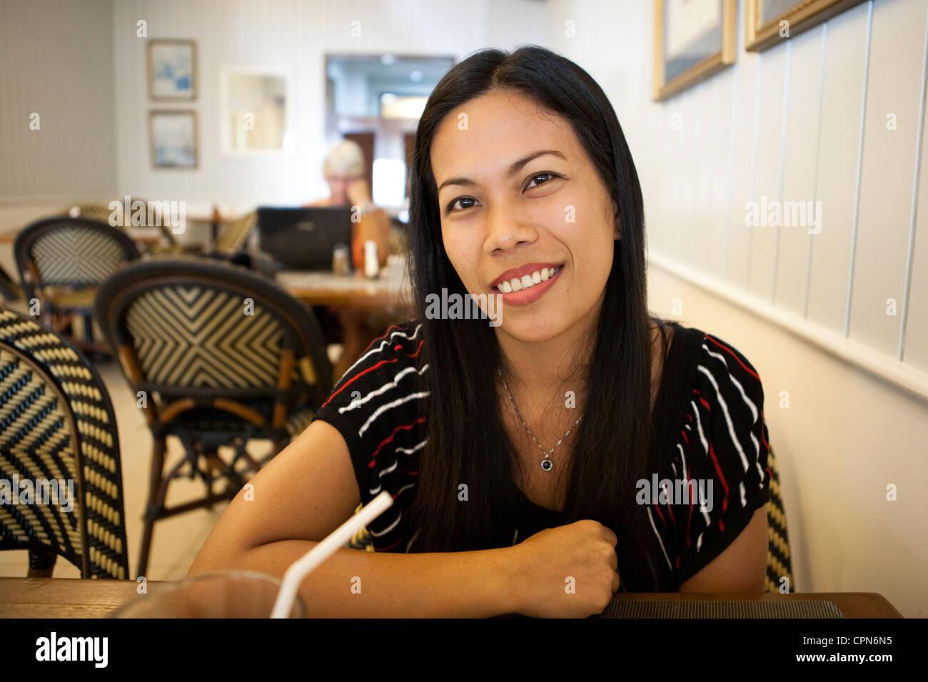 f5f7945053a Filipino woman sitting inside Cafe de France restaurant. Lapu-Lapu City
