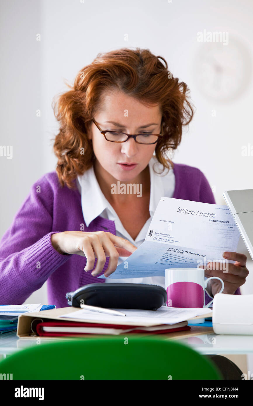 WOMAN DOING PAPERWORK - Stock Image
