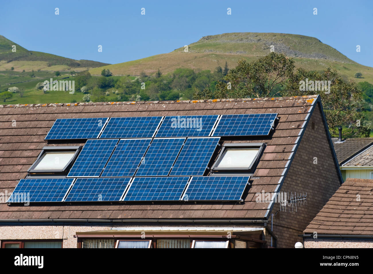 Solar panels on roof of houses in a rural housing development in Crickhowell South Wales UK Table Mountain behind - Stock Image