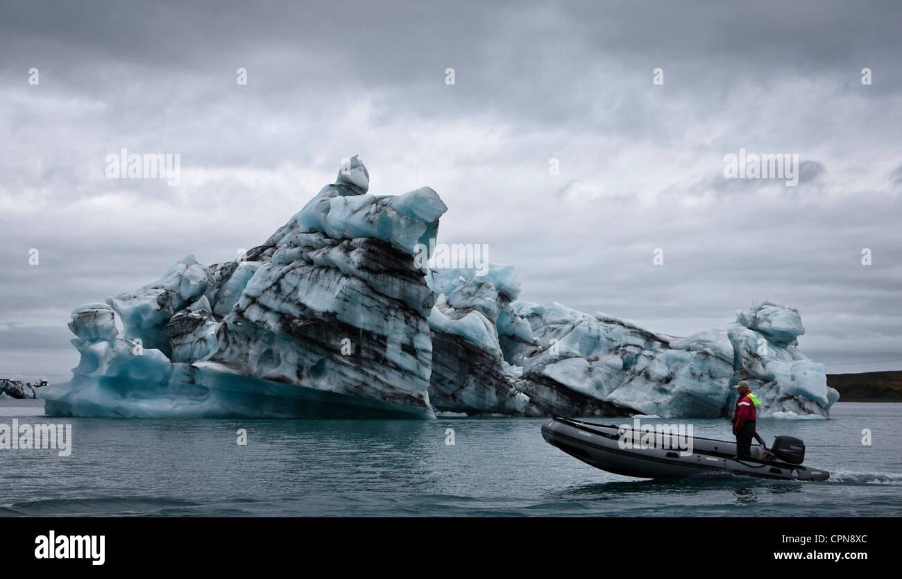 Motor boat moving past iceberg in Jokulsarlon glacial lagoon, Iceland - Stock Image