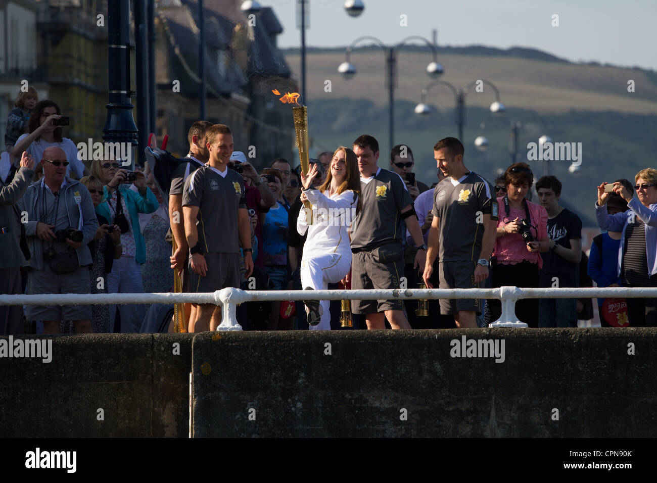 Olympic torch-bearer Carwen Richards  'kicks the bar' in Aberystwyth - Stock Image