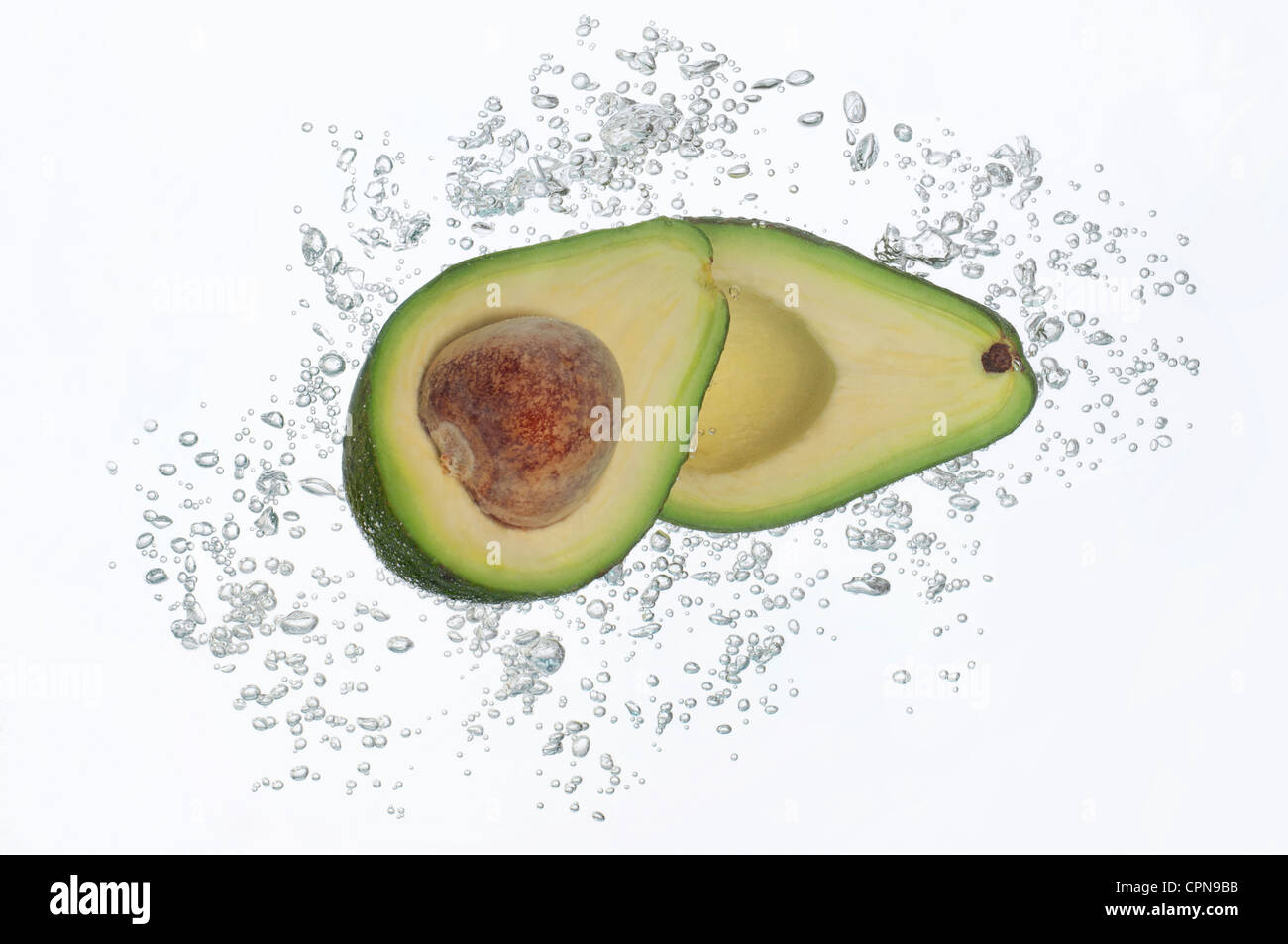 Avocado halves submerged in sparkling water - Stock Image