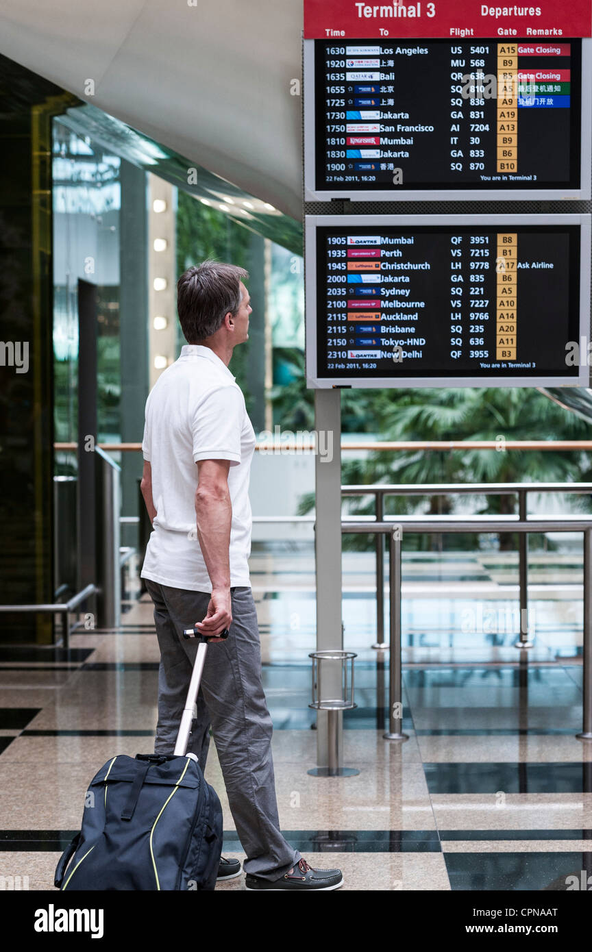 Man looking at arrival departure board in airport - Stock Image