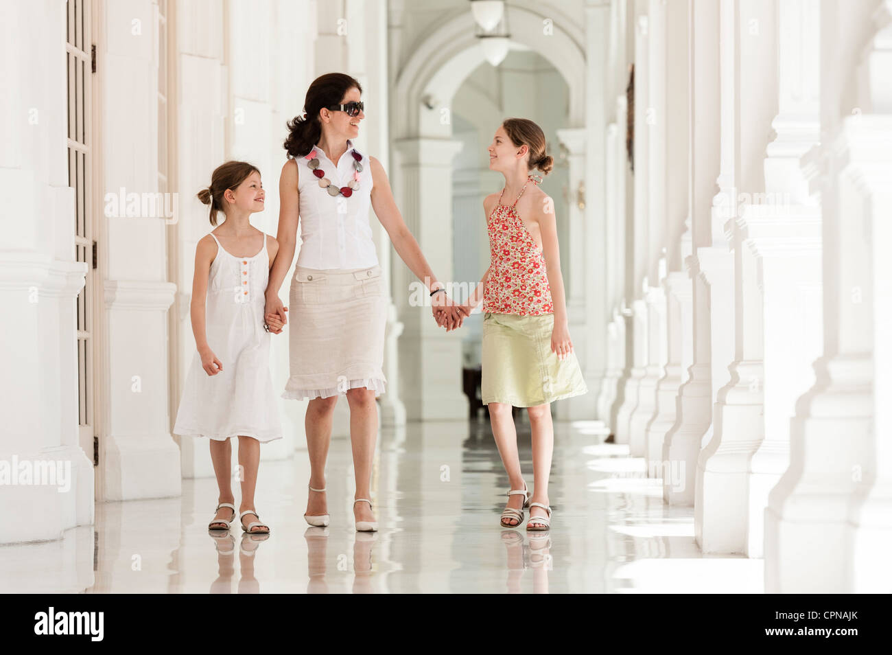 Mother and daughter walking side by side holding hands - Stock Image