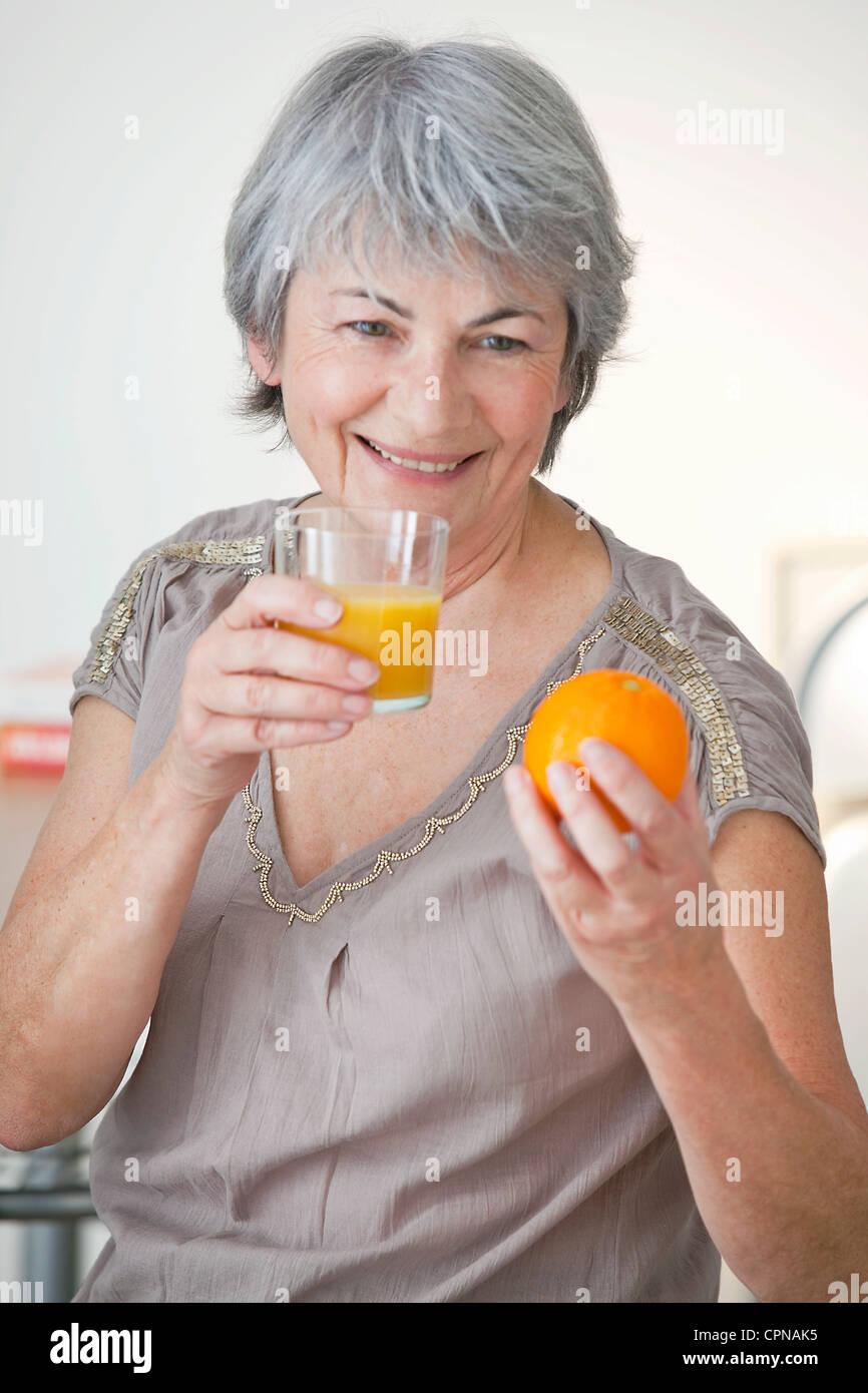 ELDERLY PERSON EATING FRUIT - Stock Image