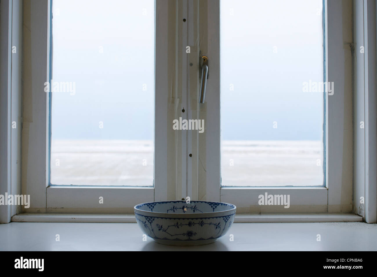 Ceramic bowl in front of window - Stock Image