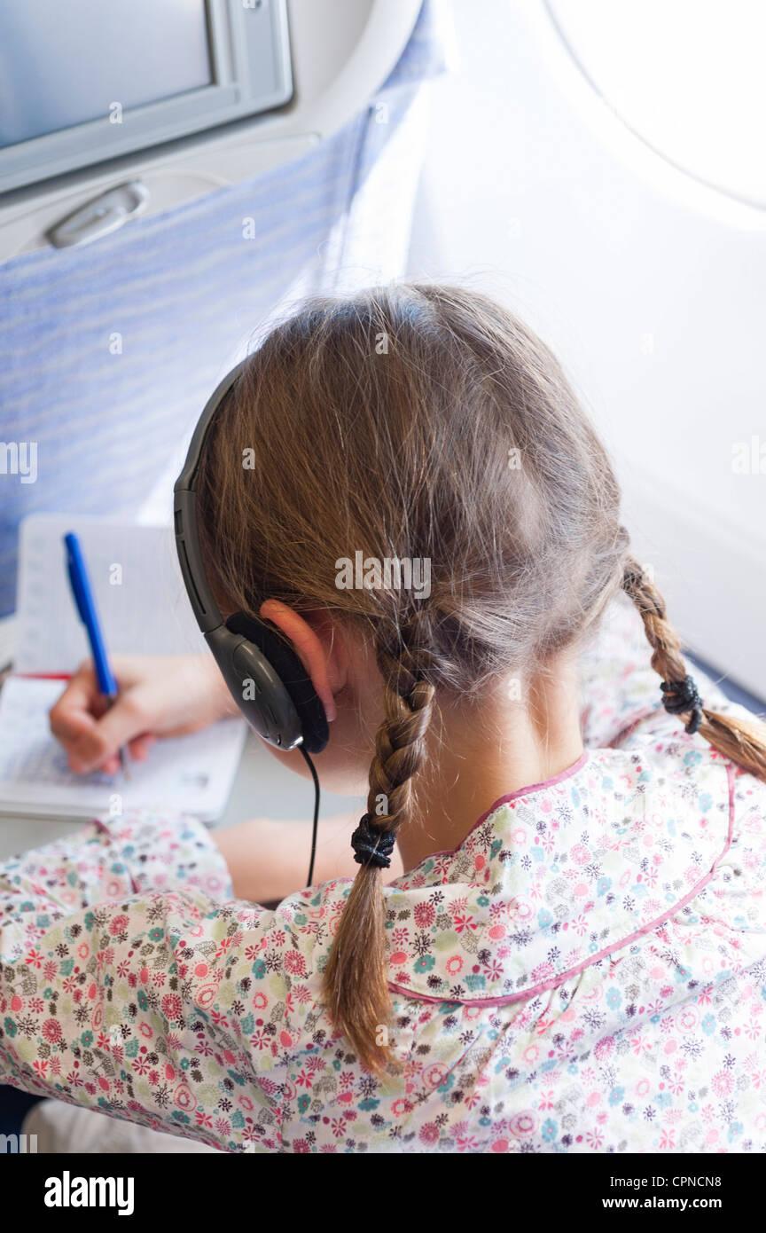 Girl writing on airplane - Stock Image