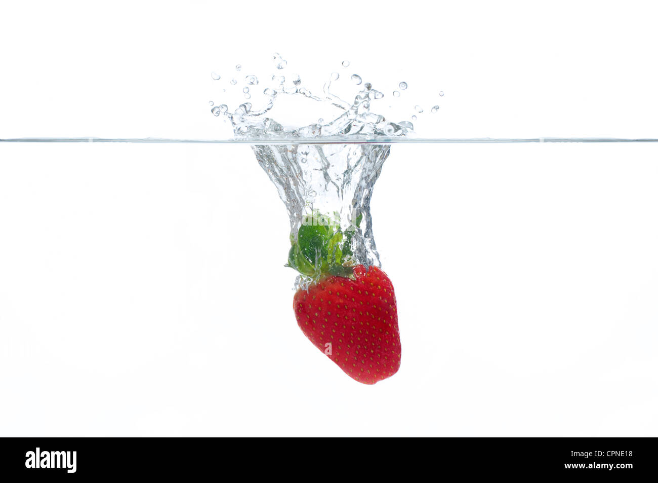 Strawberry splashing into water - Stock Image