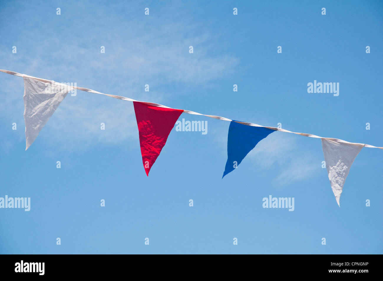 Bunting flags - red white and blue - against a blue sky. - Stock Image