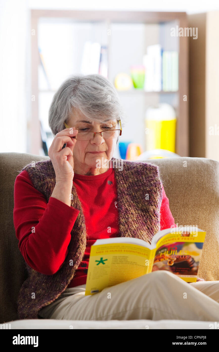 ELDERLY PERSON READING - Stock Image