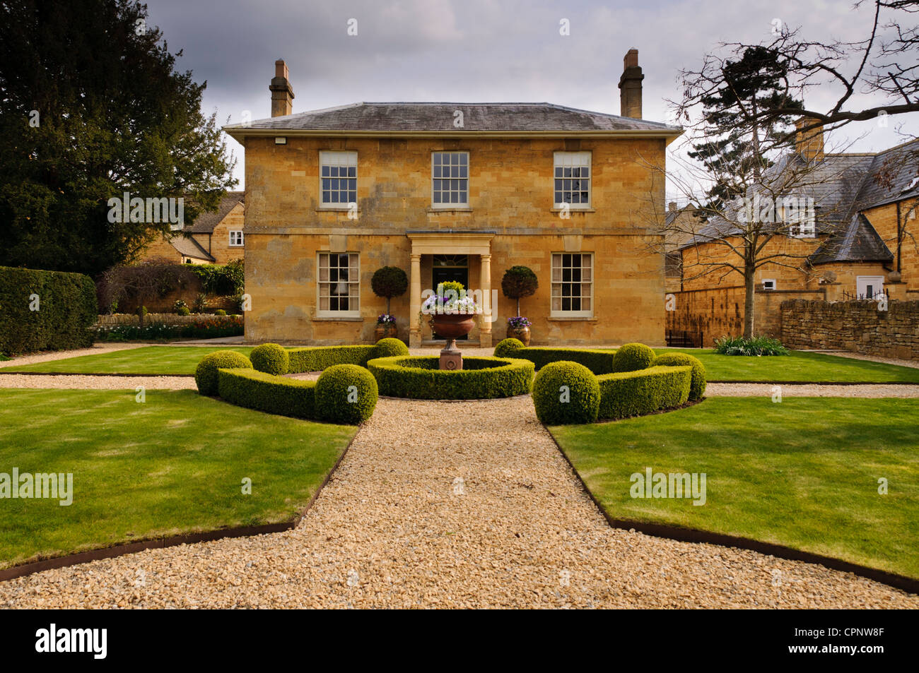 Perfectly symmetrical honey coloured Cotswold stone house and its