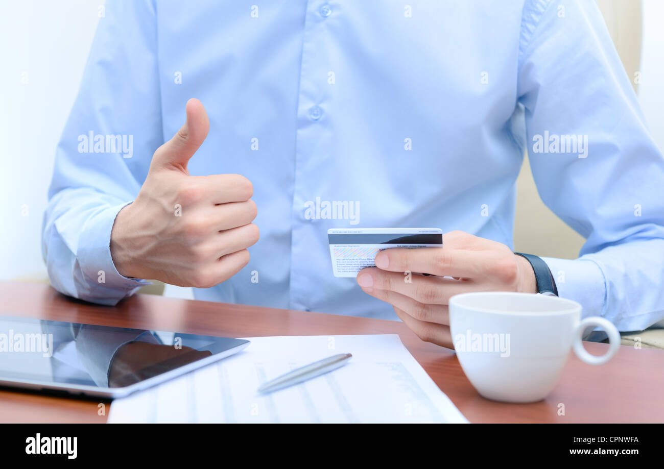 Successful businessman with a credit card in hand, sits at the workplace. - Stock Image